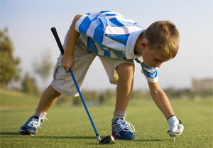 A young golfer bends over to tee up a ball